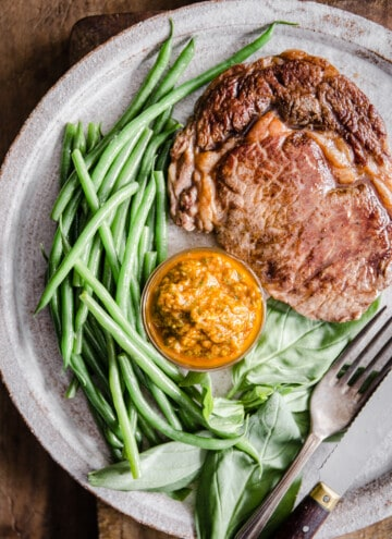 Steak with green beans and sun-dried tomato sauce on a white plate