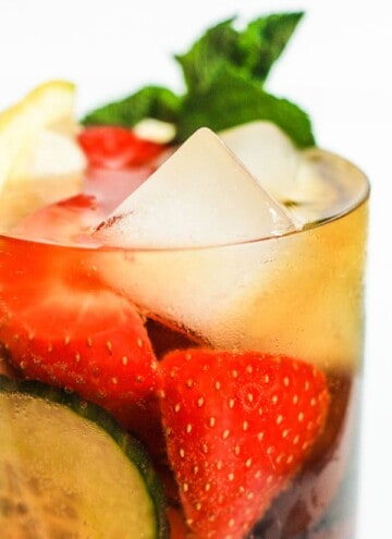 A glass of Homemade Pimms filled with fruit and ice