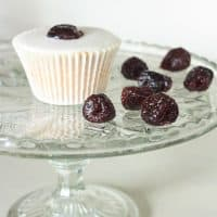 A cupcake on a cake stand next to some glacé cherries