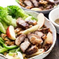 Roast Pork Belly Apple & Caramelised Walnut Salad in a white bowl on a wooden board
