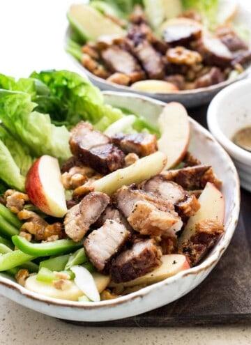 Roast Pork Belly Apple & Caramelised Walnut Salad in a white bowl on a wooden board