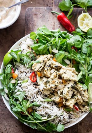 A bowl of Coronation Chicken Salad on a wooden board