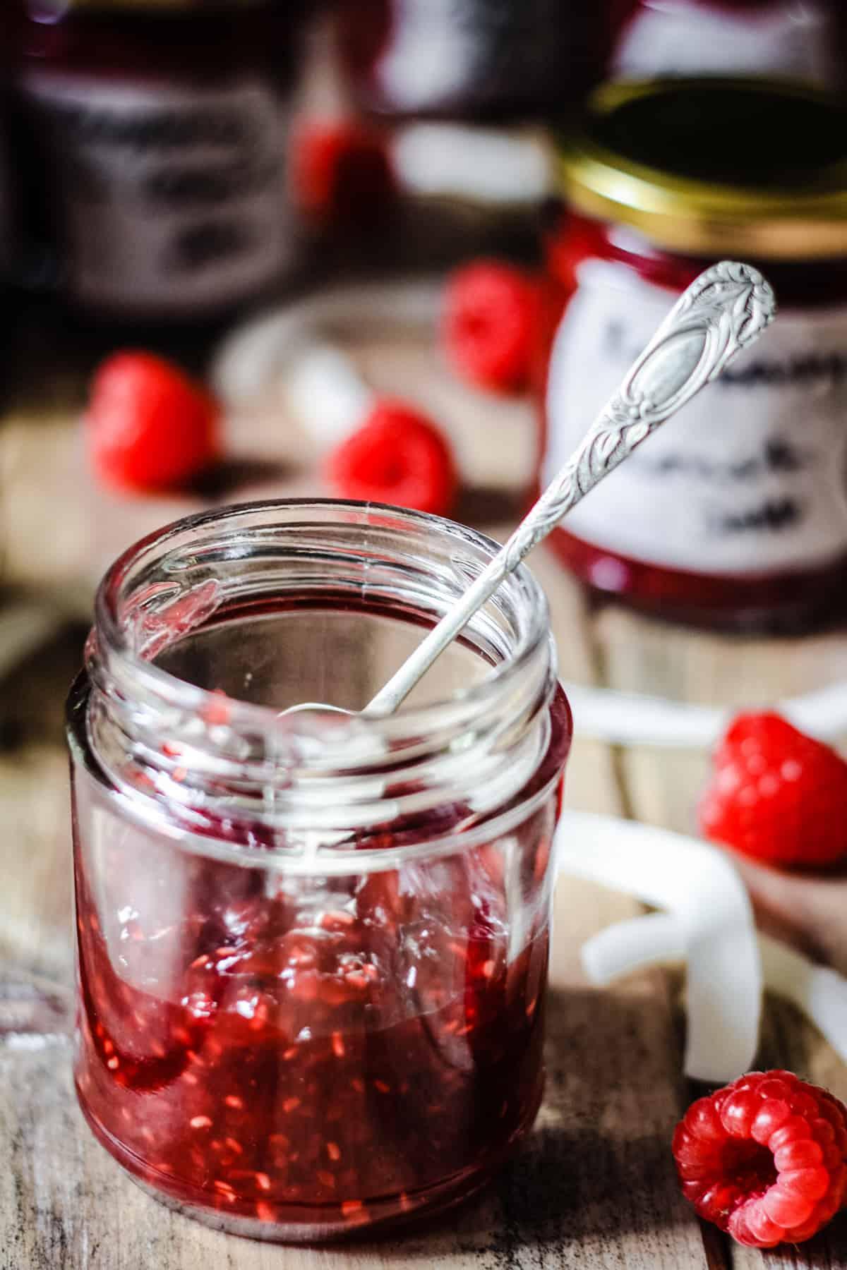 A jar of Raspberry Coconut Jam with a spoon