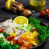 bowl of rice salad ingredients with lemon squeezer, vinaigrette and tomatoes in background