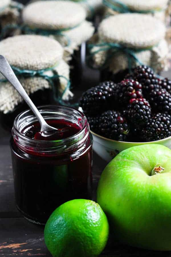 A jar of Wild Blackberry Lime Jam with a spoon in it and the ingredients surrounding