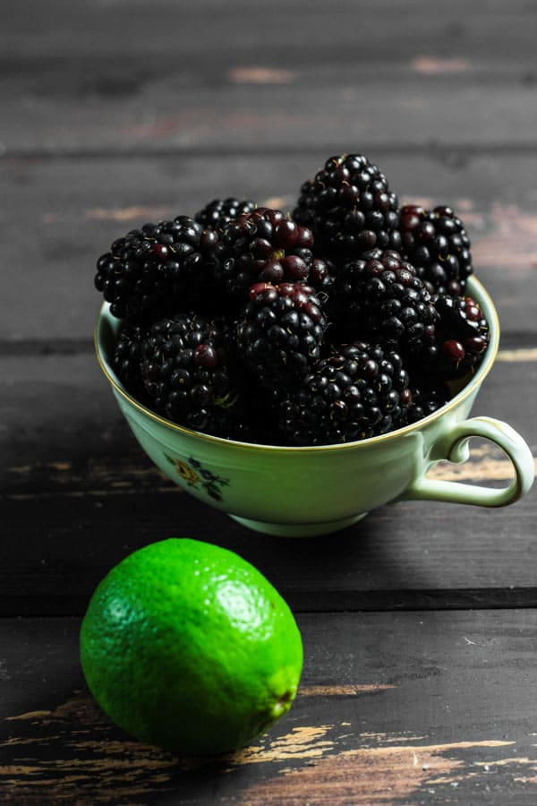 A teacup full of blackberries and a lime