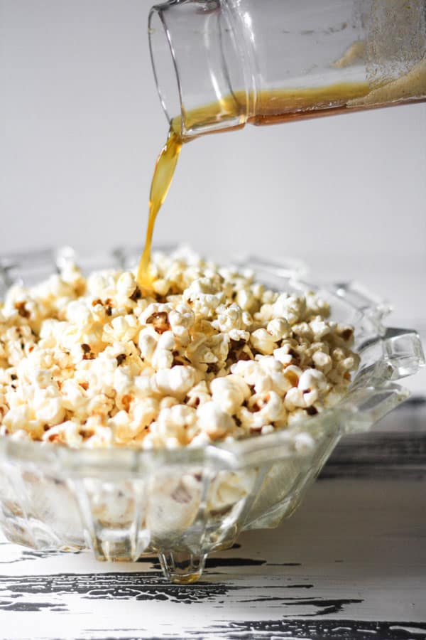 butter being poured into popcorn in a bowl on a table