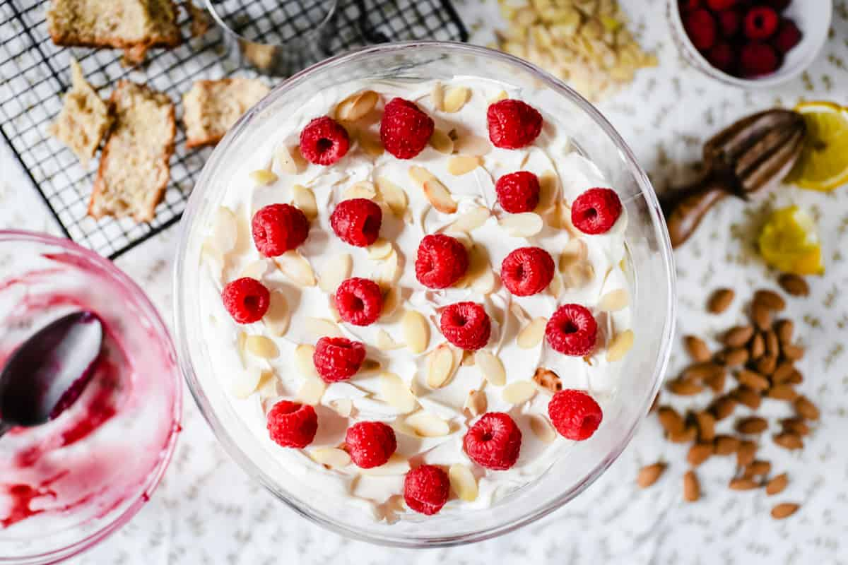 This Lemon, Almond and Raspberry Trifle is a perfectly special way to end your winter feast. A gluten-free lemon and almond sponge is drizzled with limoncello, cosseted by a thick blanket of raspberry curd and topped with dreamy lemon custard and clouds of double cream. A crunch of toasted almonds and fresh raspberries are scattered to finish.