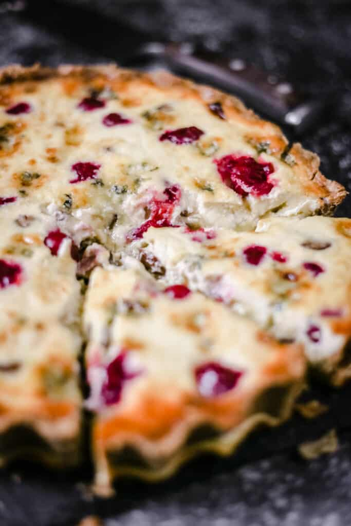 Close up image of Stilton, Chestnut and Cranberry Tart with a slice being taken out