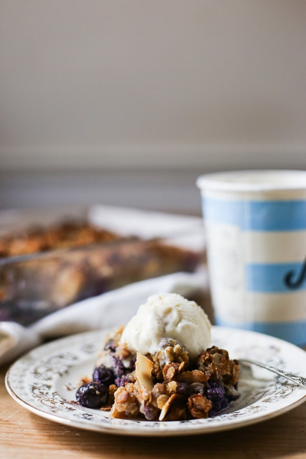 This Blueberry Ricotta Coconut Crisp is a quick gluten-free dessert to throw in the oven. Layered with plump juicy blueberries, creamy ricotta then topped with crunchy clusters of coconutty oats.