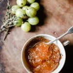 Overhead image of Gooseberry Thyme Jam on a wooden board with gooseberries and a sprig of thyme