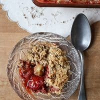 Overhead image of a bowl of Strawberry Gooseberry Crumble with a spoon