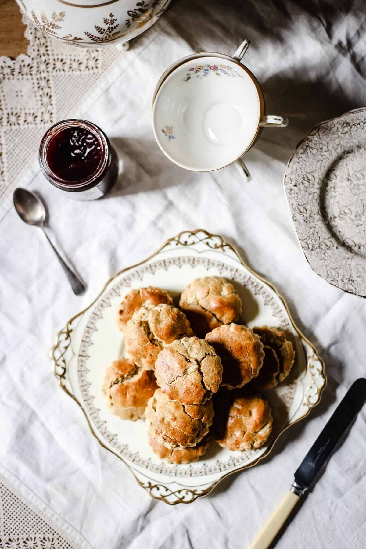 overhead image of apple scones on a china plate next to a tea set and a pot of jam