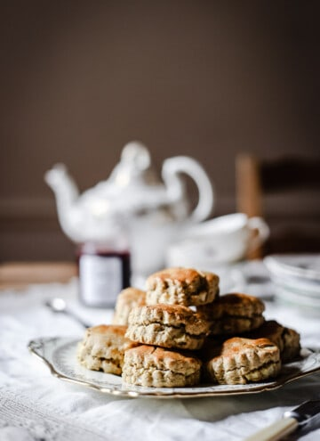 apple scones piled on a china plate in front of a tea set and a pot of jam
