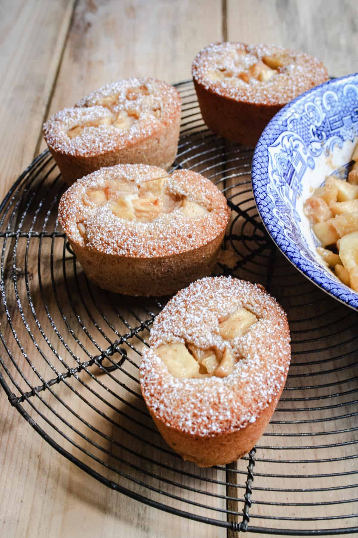 Some Apple Cinnamon Ricotta Friands sitting on a wire rack next to a bowl of caramelised apples