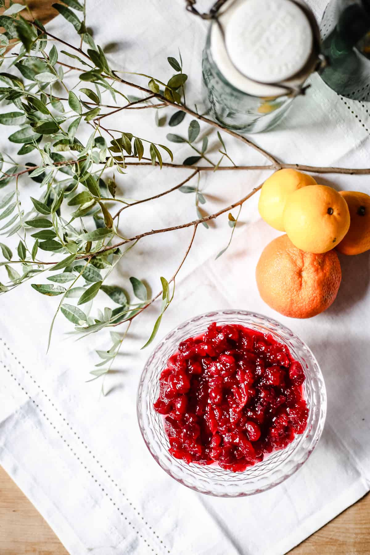 Cranberry Clementine Sauce on a white tablecloth surrounded by clementines and greenery