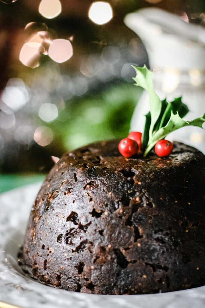 Christmas Pudding on a plate with a sprig of holly on top. In front of christmas lights