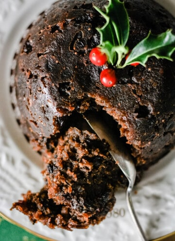 Christmas Pudding on a plate, spoon cutting into it with a sprig of holly on top.
