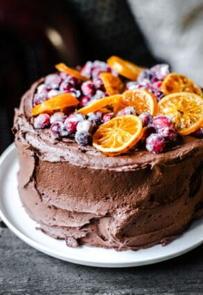 Chocolate Cranberry Clementine Cake on a white plate on a wooden board