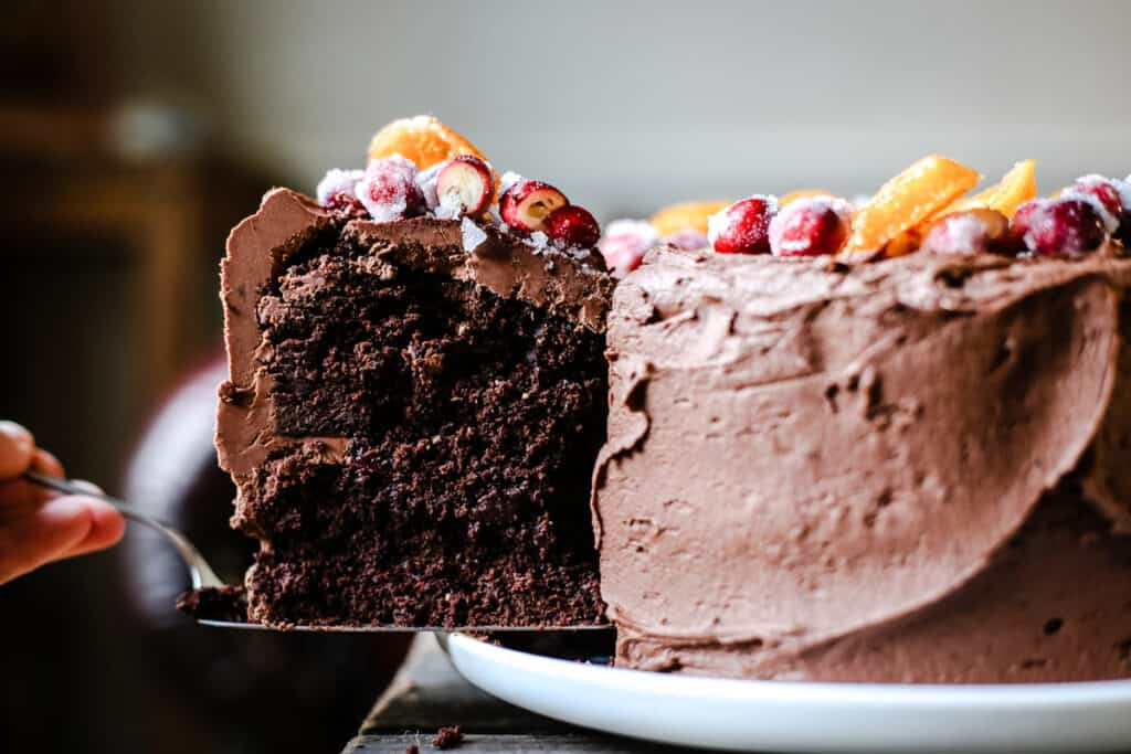 A slice being pulled out of Chocolate Cranberry Clementine Cake