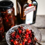 Cranberry Cointreau Mincemeat in a glass bowl next to jars of mincemeat and a bottle of cointreau on a wooden box
