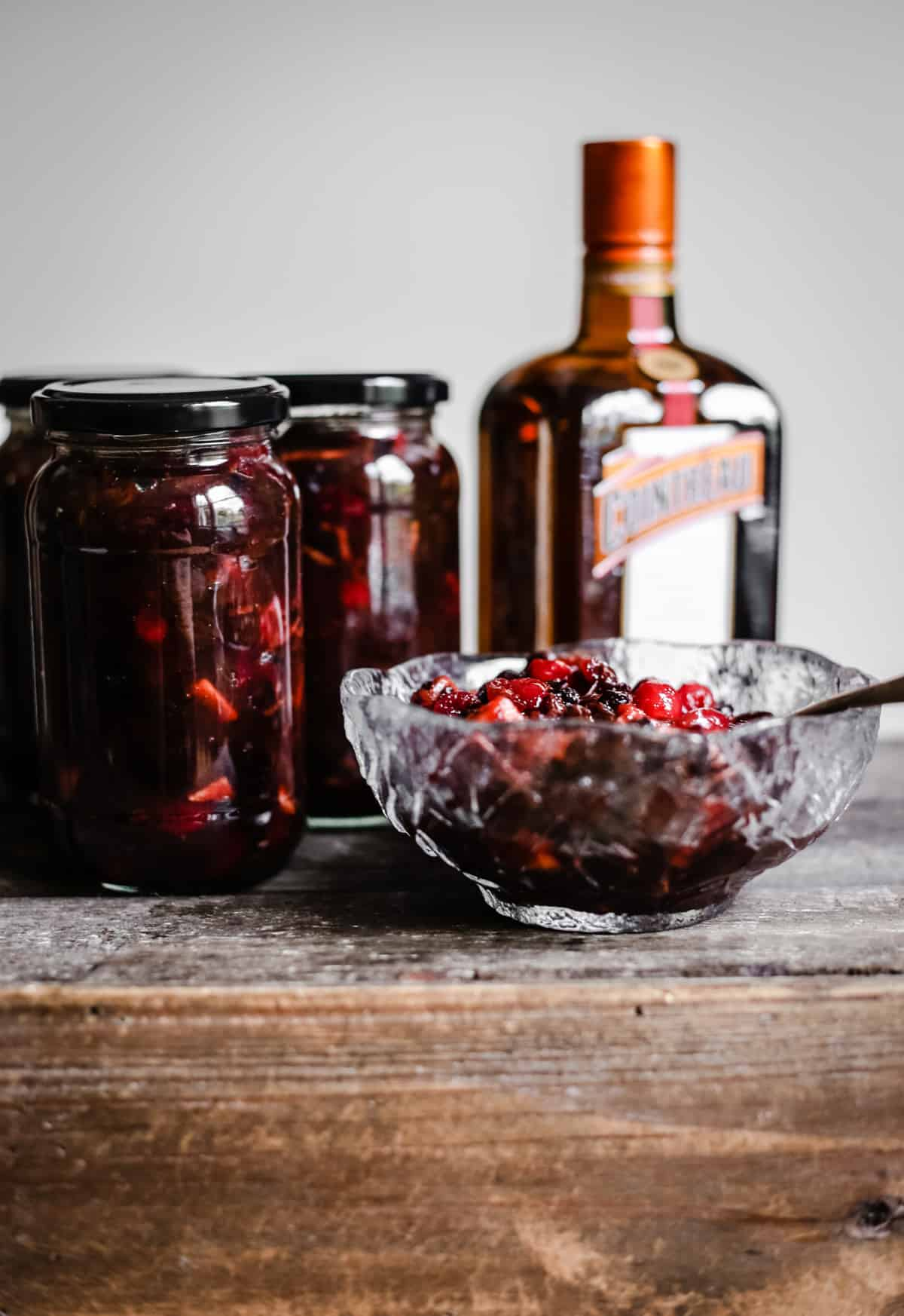 Boozy Cranberry mincemeat with cointreau in a glass bowl on a wooden table in front of cointreau and jars of mincemeat
