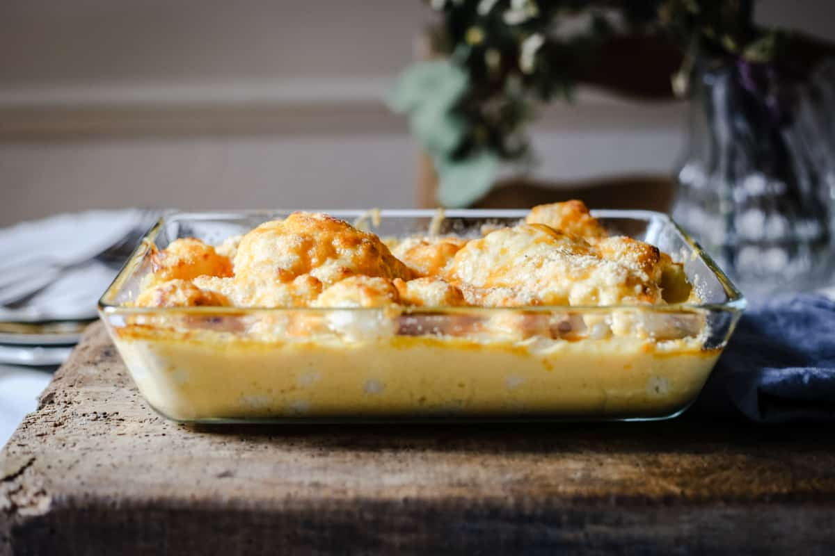 side shot of Gluten-Free Cauliflower Cheese in a serving dish on a wooden board