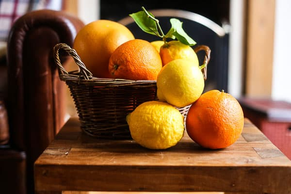 Oranges, lemons and grapefruit in or next to a basket on a wooden table