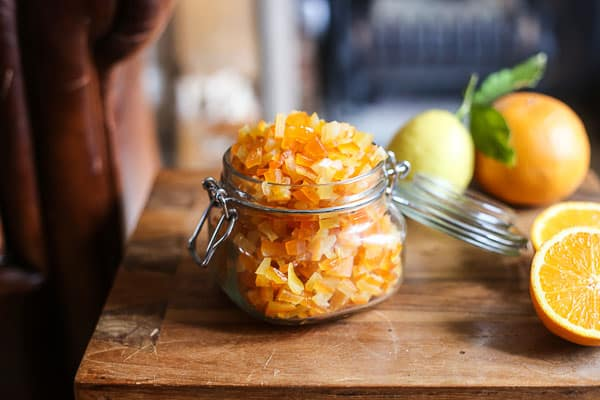 Homemade Mixed Peel in a jar on a table surrounded by citrus fruits