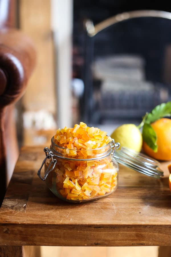 Homemade Mixed Peel in a jar on a wooden table surrounded by citrus fruits