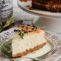 A slice of Goats Cheese, Honey and Thyme Cheesecake on a plate next to a pot of honey and the whole cheesecake
