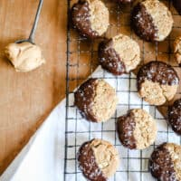 Gluten-Free Chocolate-Dipped Oat Peanut Butter Cookies on a wire rack next to a spoon of peanut butter