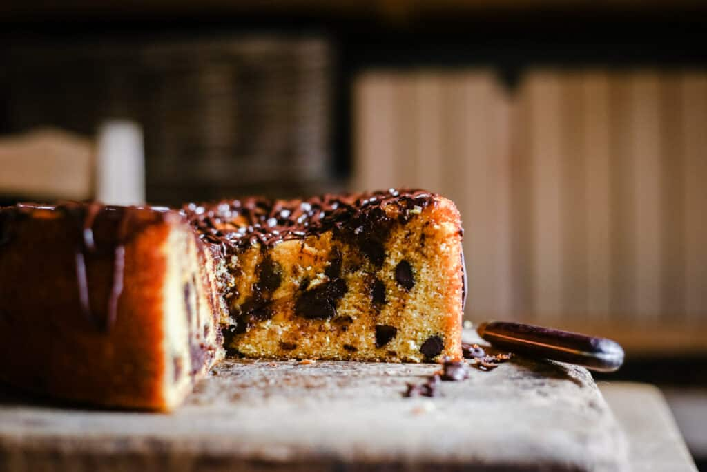 Whole Orange Chocolate Chip Cake on a wooden board with a slice taken out