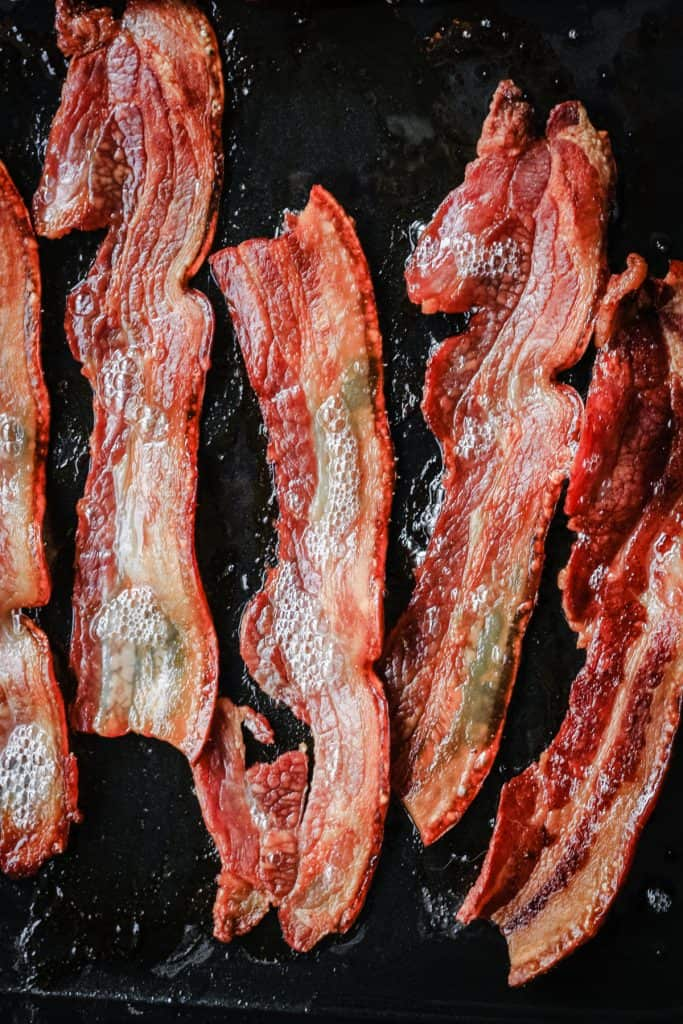 Roasted bacon sizzling in a pan