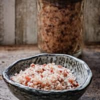 A small bowl of bacon salt in front of a jar of bacon salt