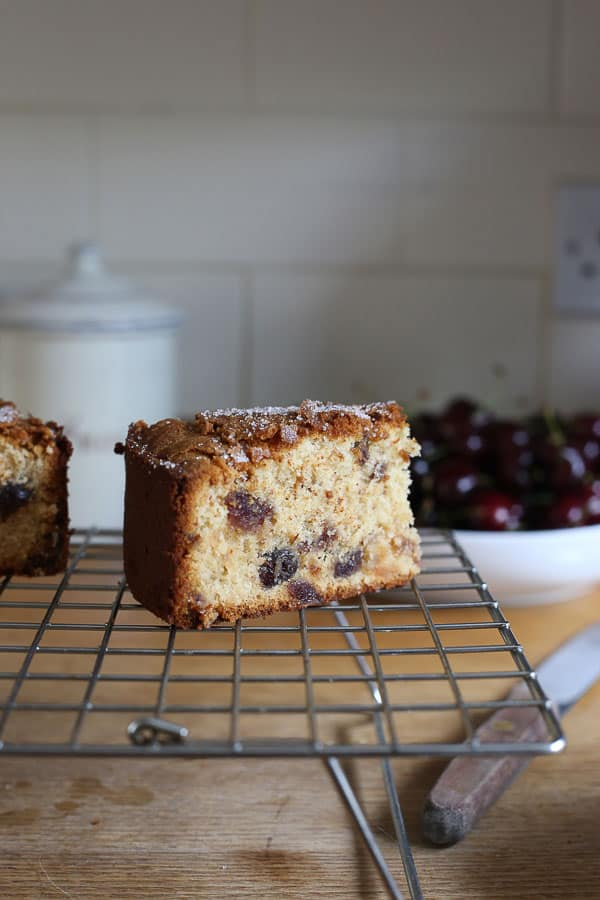 A slice of cherry cake on a cooling rack with a cake knife sitting in front of a bowl of cherries