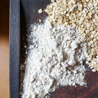 Image of jumbo rolled oats and gluten-free oat flour on a wooden board