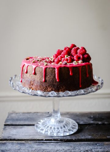 Raspberry Pistachio Cake sitting on a cake stand on a wooden table