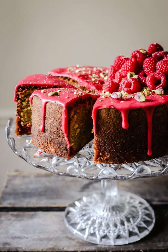 Sliced Raspberry Pistachio Cake sitting on a cake stand on a wooden table