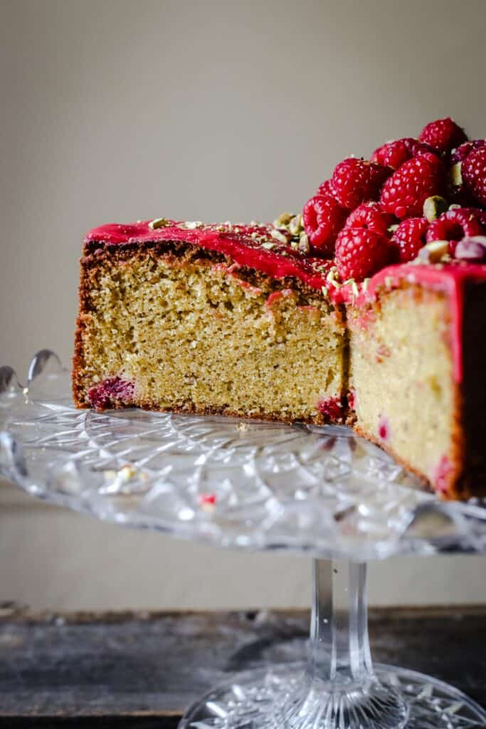 A cut Raspberry Pistachio Cake sitting on a cake stand on a wooden table