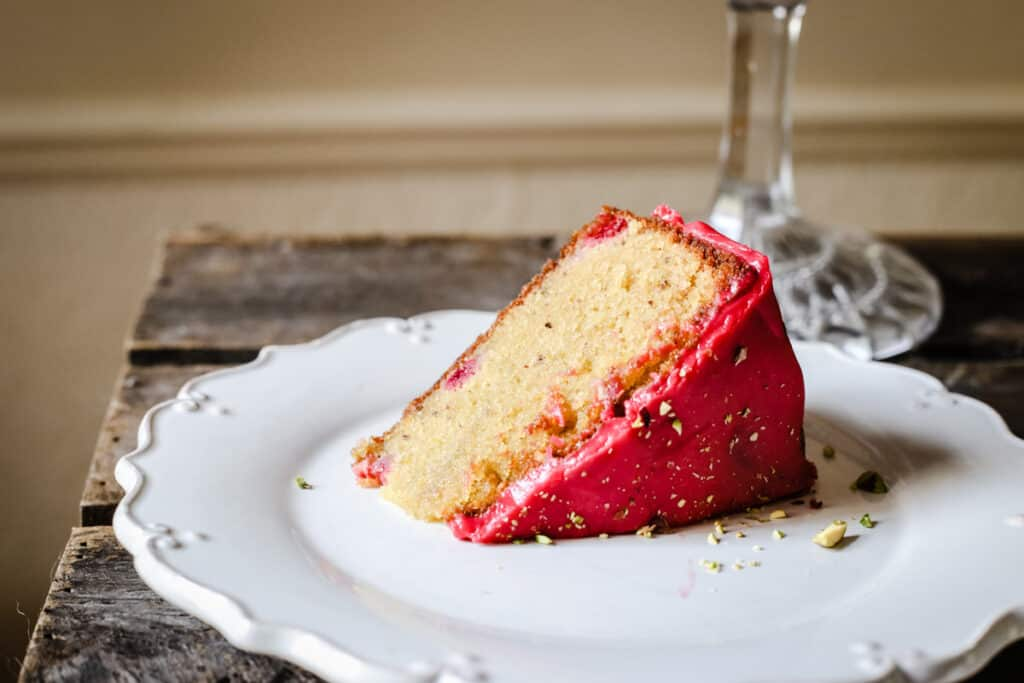 A slice of Raspberry Pistachio Cake on a white plate on a wooden table
