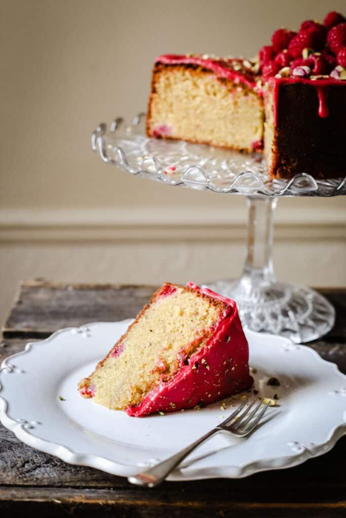 A slice of Raspberry Pistachio Cake on a white plate with a fork on a wooden table in front of a cake stand with cake on it