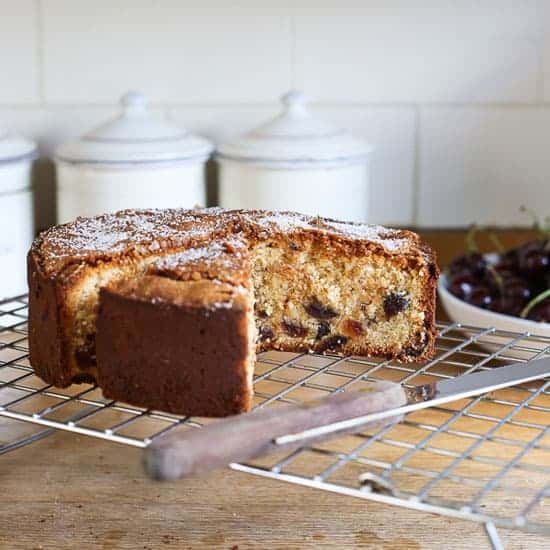 Cherry Cake on a cooling rack with a cake knife sitting in front of a bowl of cherries