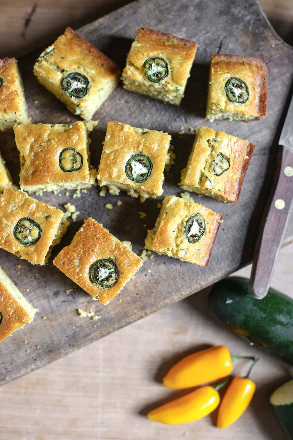 overhead shot of Jalapeno Honey Courgette Cornbread on a wooden board with a knife next to courgette and jalapenos
