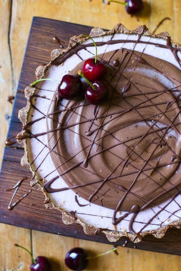 No-Bake Frozen Cherry Chocolate Pie on a wooden board on a wooden table with cherries
