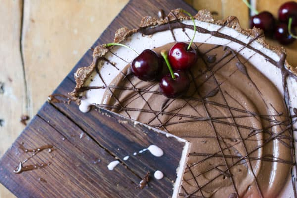 No-Bake Frozen Cherry Chocolate Pie with slices cut on a wooden board on a wooden table with cherries