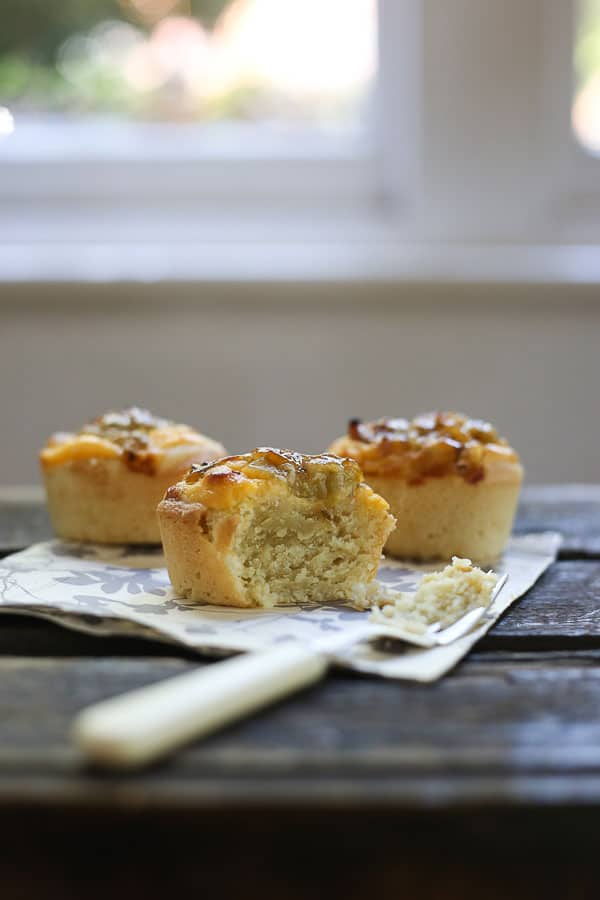 gooseberry friands with a bite taken out on a napkin with a fork on a wooden table