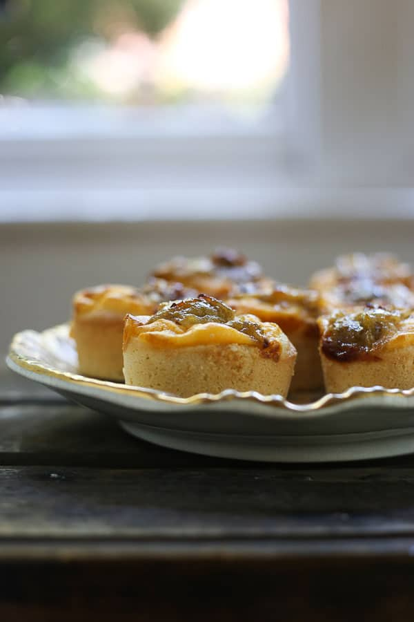 gooseberry friands on a plate on a wooden table in front of a window