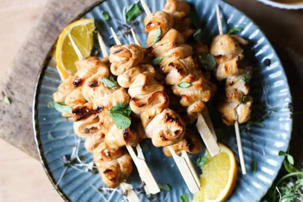 Honey Orange & White Wine Chicken Skewers on a plate with oranges, micro herbs