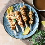 Honey Orange & White Wine Chicken Skewers on a plate with oranges, microherbs next to a bowl of marinade and a jar of honey
